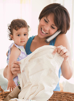 Mother folding laundry while holding a child