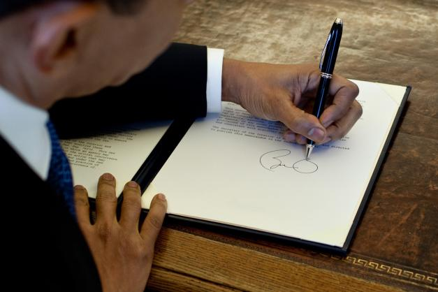 Obama signing a document