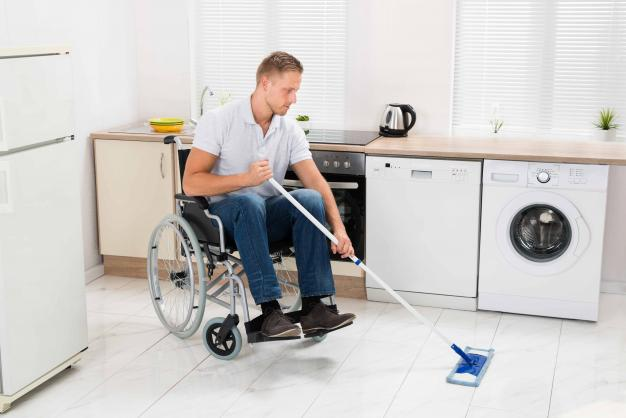 Man in wheelchair mopping the floor