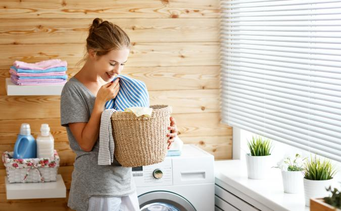 Woman smelling basket of clean laundry