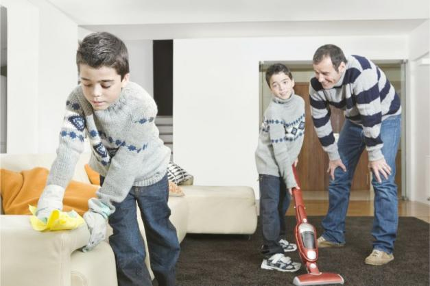 Father and two sons cleaning the living room