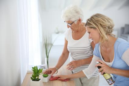 Woman helping senior clean the house