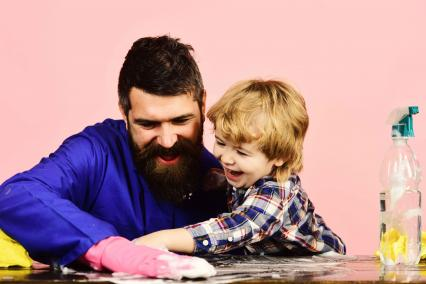 Man and child cleaning a table together