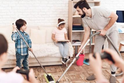 Father cleaning the house with his kids