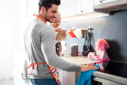 Father carrying child while cleaning the kitchen