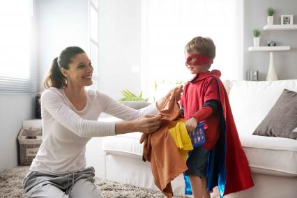Child in superhero costume helping with laundry